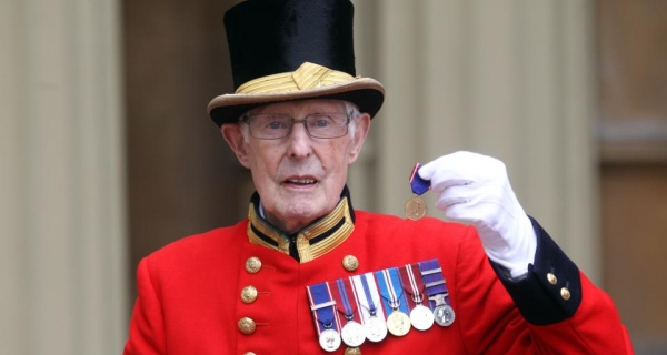 Pat Carroll poses with the medal he received from the queen for his 60 years of service at Buckingham Palace.